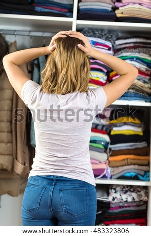 Rear view of young woman standing in front of her closet trying to find perfect outfit. She is holding her head and thinking how she does no??t have anything to wear.