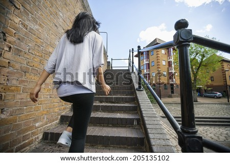 Rear view of young woman walking up stairs outdoors - stock photo