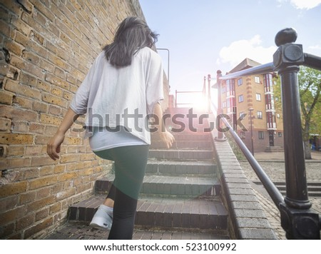 Rear view of young woman walking up stairs outdoors