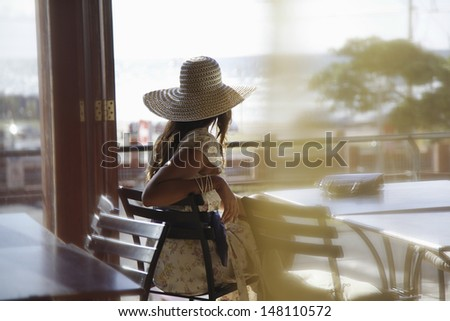 Rear view of young woman wearing sunhat at cafe - stock photo
