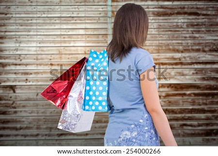 Rear view of young woman with shopping bags against wooden planks - stock photo