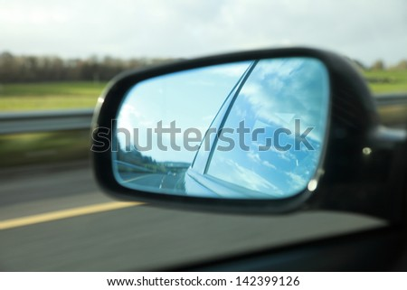 Rear view on a car mirror reflecting road - stock photo