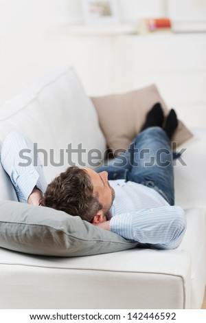 Rear view on mature man with hands behind head lying on couch at home - stock photo