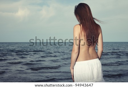 Rear view on the lonely woman feeling sad at the sea - stock photo