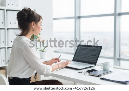 Rear view portrait of a businesswoman sitting on her workplace in the office, typing, looking at pc screen. - stock photo