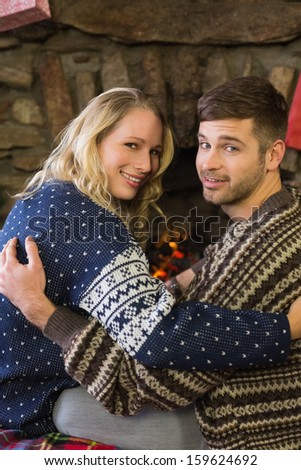 Rear view portrait of a romantic young couple smiling in front of fireplace
