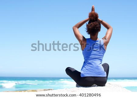 Rear view portrait of fitness woman sitting in yoga pose at the beach  - stock photo