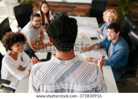 Rear view portrait of man explaining business ideas to colleagues during a meeting in conference room.  Young people meeting in boardroom. - stock photo