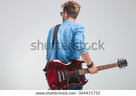 rear view portrait of young artist holding a guitar in studio while looking away