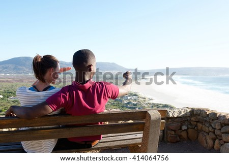 Rear view portrait of young couple sitting on a bench with man pointing at the sea, young couple on vacation. - stock photo