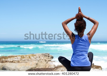 Rear view portrait of young woman sitting at the beach in yoga pose   - stock photo