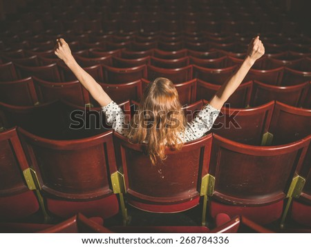Rear view shot of an excited young woman sitting alone in an auditorium with her arms raised - stock photo
