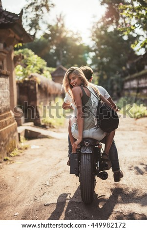 Rear view shot of young couple riding motorcycle on rural road. Beautiful young female sitting on back of her boyfriend riding bike. - stock photo