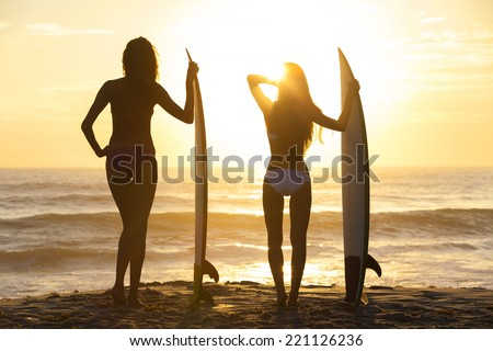 Rear view silhouettes of beautiful sexy young women surfer girls in bikinis with surfboards on a beach at sunset or sunrise - stock photo