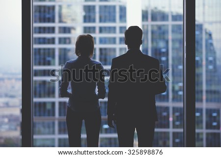 Rear view silhouettes of two business partners looking thoughtfully out of a office window in situation of bankruptcy,team of businesspeople in fear or risk watching cityscape from skyscraper interior - stock photo
