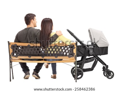 Rear view studio shot of a young parents sitting on a bench with their baby isolated on white background - stock photo