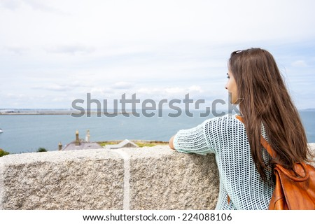 Rear view traveling woman looking at coast - stock photo