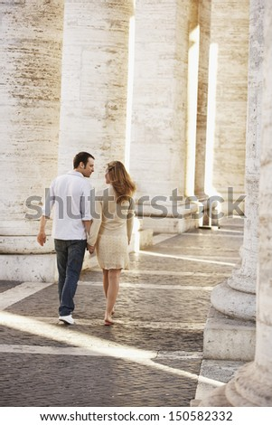Rear view young couple walking between pillars in Rome; Italy - stock photo