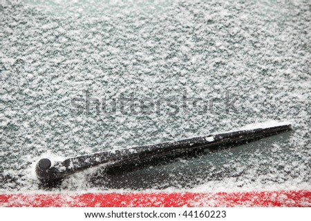 rear windscreen wiper on a car covered with snow - stock photo