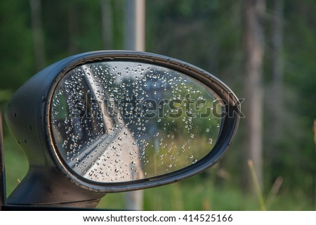 rearview mirror of car on the road in the rain