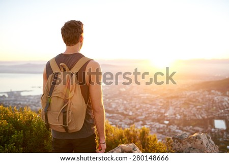 Rearview of a young man with a backpack watching the sunrise from a nature trail above the city - stock photo