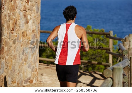 Rearview shot of a sporty adult man running down mountain trail at coastline outdoors - stock photo