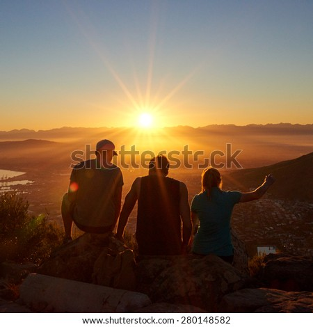 Rearview silhouettes of three friends sitting together on a nature trail watching a golden sunrise