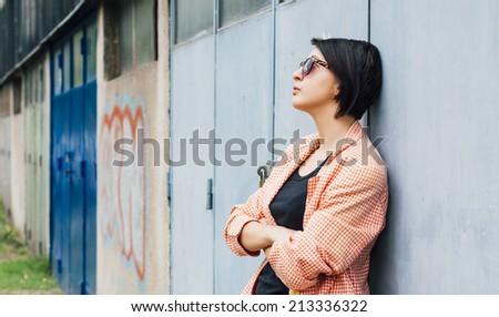 Rebellious teenager posing in front of garage door - stock photo
