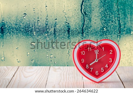 rec clock on wooden table with water droplet on glass window background