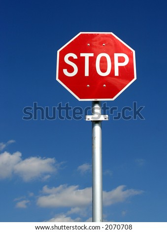 Rec & white U.S. style stop sign on a pole against a deep blue sky...some clouds in the lower frame. - stock photo