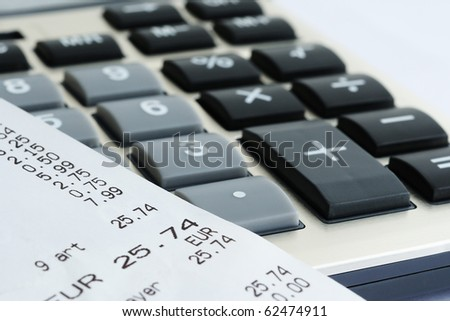 Receipt or bill from shop on gray calculator - stock photo