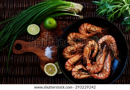 Recent large king prawns cooked in a pan, lay next to lemon and lime, rosemary and chives, Best fried shrimp appetizer to the cold beer