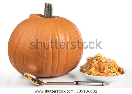 Recently cleaned pumpkin with seeds in bowl and large spoon, ready for carving