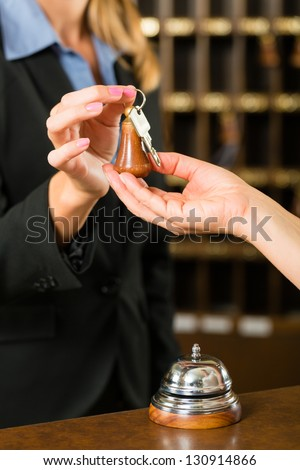 Reception - Guest checking in a hotel at the front desk, the room key is handed over
