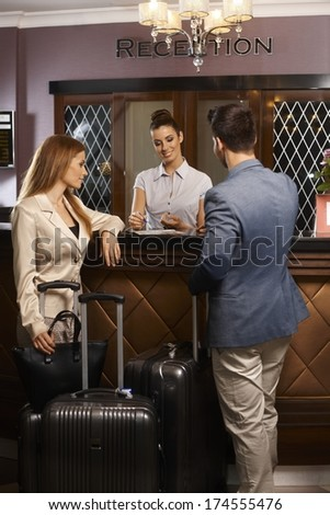 Receptionist giving information to guests upon arrival at hotel. - stock photo