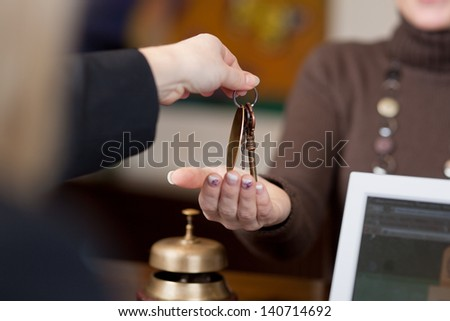 Receptionist giving room keys to customer at reception in hotel - stock photo