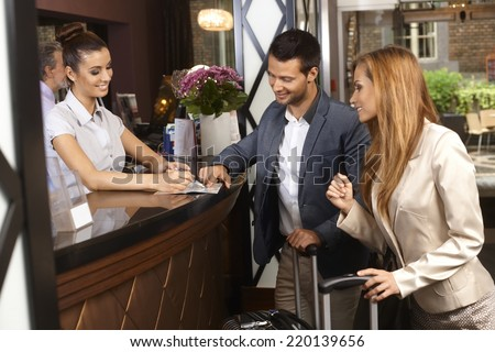 Receptionist giving tourist information to hotel guests upon arrival. - stock photo