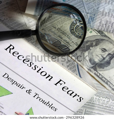 Recession fears headlines. Magnifying glass and one hundred dollar bill in the background. - stock photo