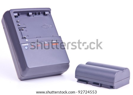recharged battery and charge device on white background in studio - stock photo