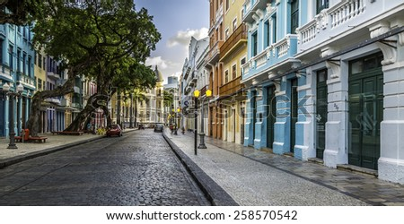 RECIFE, BRAZIL - MARCH 10, 2014: Panoramic view of Recife in PE, Brazil showcasing the architecture of the  Rua do Bom Jesus with its cobble stones and some locals passing by on March 10, 2014. - stock photo