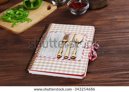 Recipe book and ingredients for cooking on a table in kitchen - stock photo