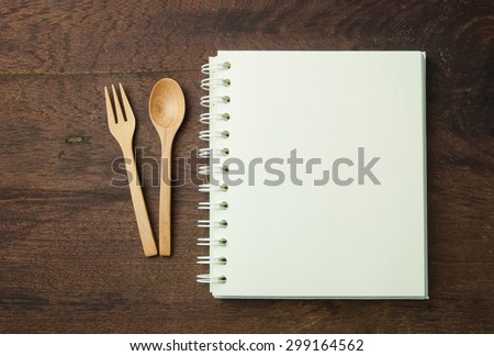 recipe book and spoon,fork on wooden table. - stock photo