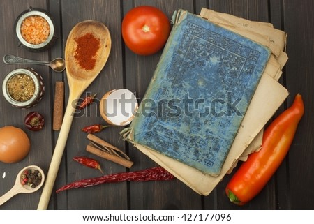 Recipe book and vegetables. Chili pepper and tomatoes. Food preparation according to the old recipe book. Grandma's recipe book. Old recipes for cooking. - stock photo