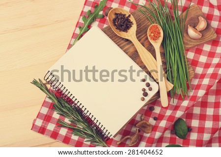Recipe book page with different herbs on napkin wooden background - stock photo