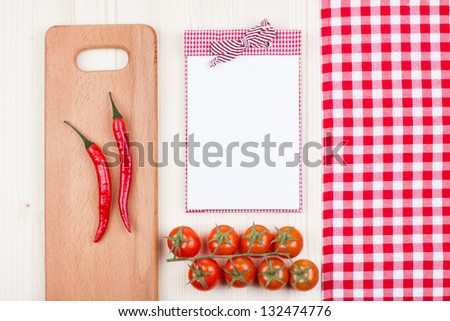 Recipe cookbook, checkered tablecloth, cherry tomatoes, chili, plank on wood background - stock photo