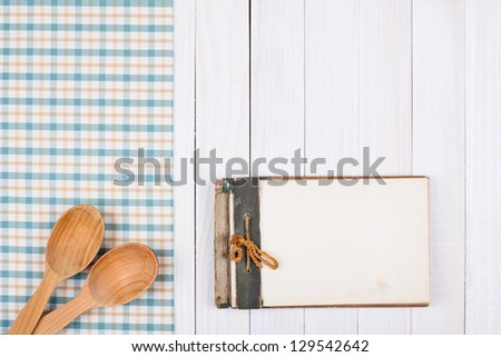 Recipe notebook, tablecloth on white wood background - stock photo