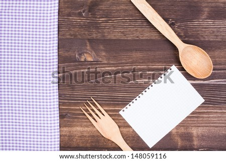 Recipe paper, spoon, fork, tablecloth on wood background - stock photo
