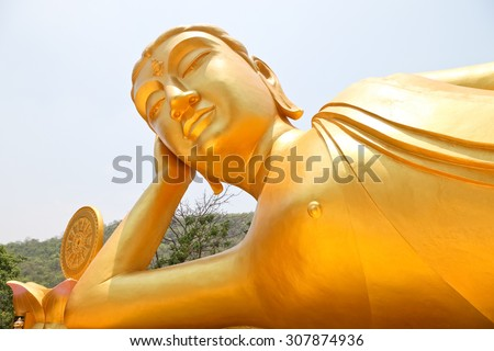 Reclining Buddha gold statue ,Reclining Buddha gold statue at temple Kanchanaburi, Thailand soft focus - stock photo