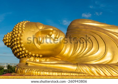 Reclining Buddha statue on blue sky - stock photo