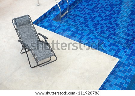 Reclining chair along a swimming pool - stock photo
